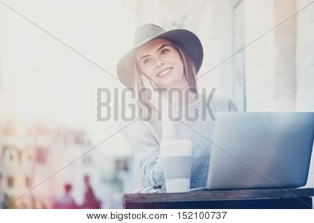 Pleasant time spending . Joyful content beautiful woman smiling and standing outside the cafe while talking on cell phone