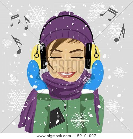 young woman wearing winter clothes listening to music with headphones in the winter under snowfall