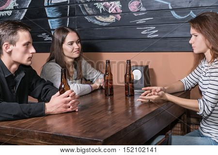Man and two women sitting at a wooden table with bottles of beer and talk