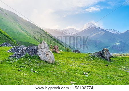 The meadow at the mountain foot in Sno village is occupied with the boulders with carved faces of most famous Georgian cultural figures Kazbegi Georgia.