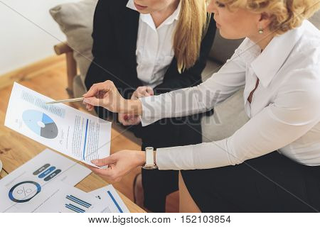 Colleagues are discussing document with concentration. Women are sitting on couch in office