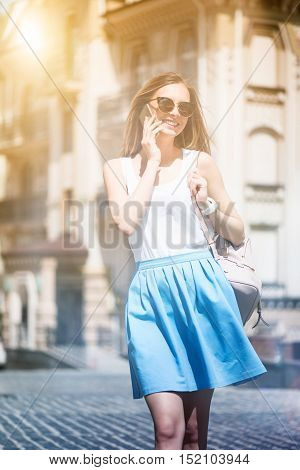 Best way to relax. Cheerful delighted woman talkign on cell phone and walking in the city while expressing gladness