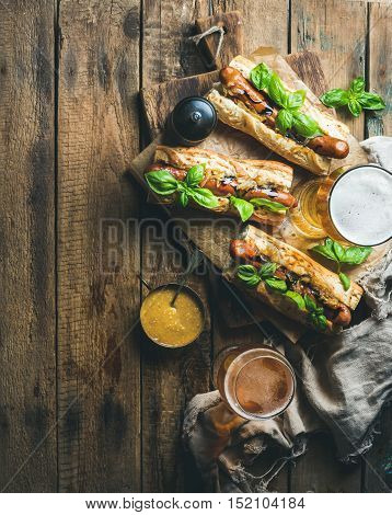Glasses of wheat unfiltered beer and homemade grilled sausage dogs in baguette with mustard, caramelised onion and herbs on serving board over rustic wooden background, top view, copy space