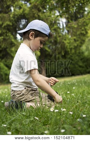Playing boy on lawn. Funny white child with baseball cap. Young lad sits in grass. Youngster with thoughtful face. In captivity of activity. Son spends leisure time activities in house garden.