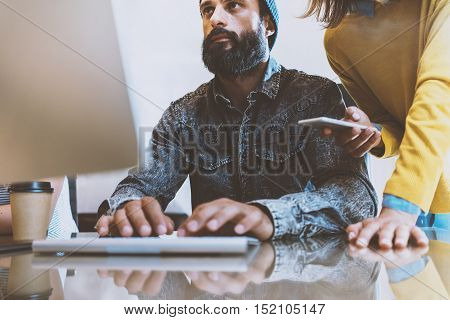 Bearded man working in the office.Coworker typing at a computer keyboard. Woman standing near him and holding smartphone her hand.Horizontal, blurred