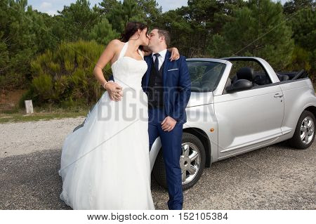 Lovely cute groom and bride on a grey convertible car posing