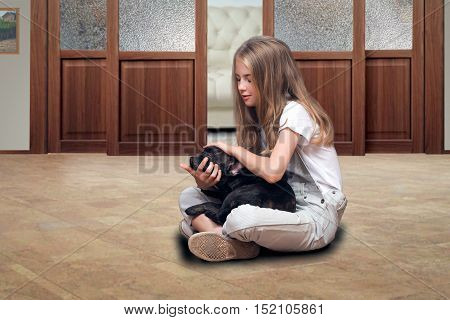 Teen girl sitting on the floor in the room and stroked the little French bulldog puppy. Dog sleeping