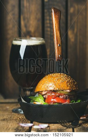Homemade beef burger with crispy bacon, fresh vegetables and tomato sauce with knife thrust inside in cast iron pan served with glass of dark beer on rustic wooden background, selective focus