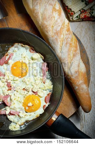 Fried eggs in a frying pan with bread for breakfast