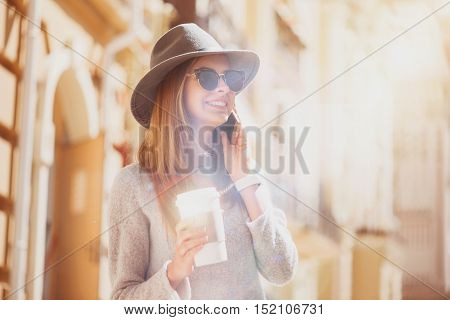 Nice to ear you. Cheerful charming young woman talking oncell phone and drinking coffee while walking in the city
