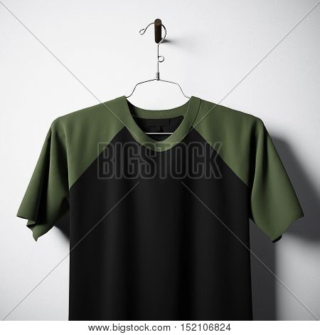 Closeup of blank black and green cotton tshirt hanging in center of empty concrete wall. Clear label mockup with highly detailed textured materials. Square. Front side view. 3D rendering