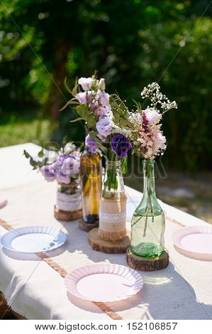 Decoration of a wedding table of newlyweds: the flower compositions and bottles decorated in style a rustic.