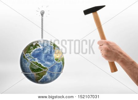 Close up view of a man's hand driving a nail into wall with the Earth hunging on it isolated on white background. Ecology and environment. Natural resources. Elements of this image are furnished by NASA.