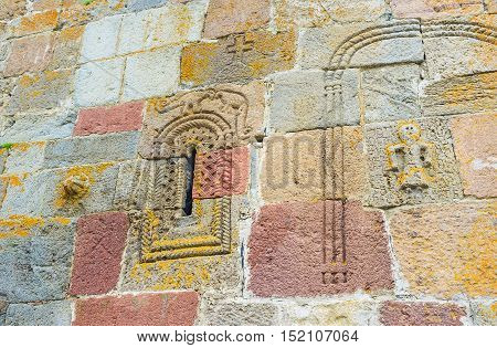The wall of Tsminda Sameba (Holy Trinity) Church with the old preserved carved ornamentations and depiction of the ancient dinosaurs above the window Gergeti Georgia.