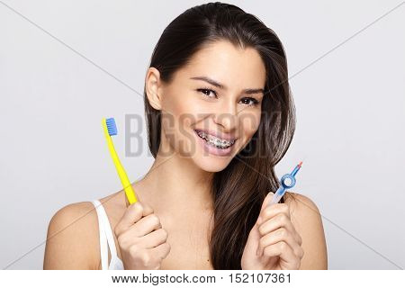 Young woman with braces and toothbrush and braces brush cleaner