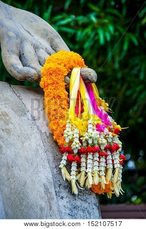 Bunch of garland on the hand of Buddha image statue.