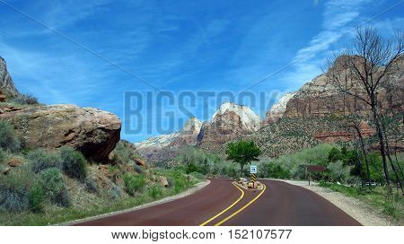 A road lined by mountains, rocks and preserved nature through the Zion Park in Utah, USA. Natural colors and light.
