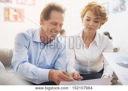 Successful mature businessman is explaining his ideas about project to colleague. He is pointing at document and smiling. Woman is sitting and listening to him attentively