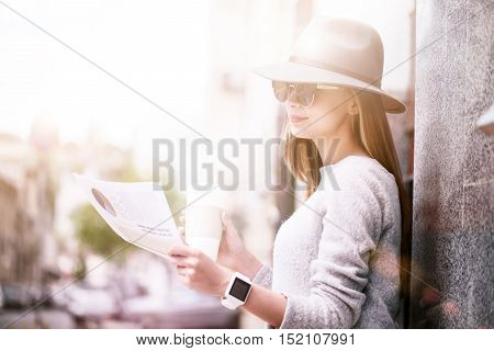 Informational whirlwind. Content beautiful young woman drinking coffee and reading newspaper while resting outside