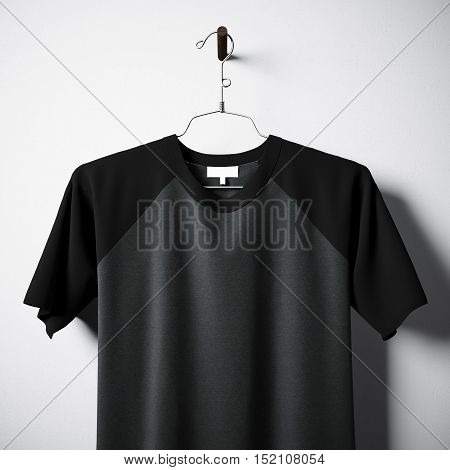 Closeup of blank cotton tshirt of black and gray colors hanging in center of empty concrete wall. Clear label mockup with highly detailed textured materials. Square. Front side view. 3D rendering