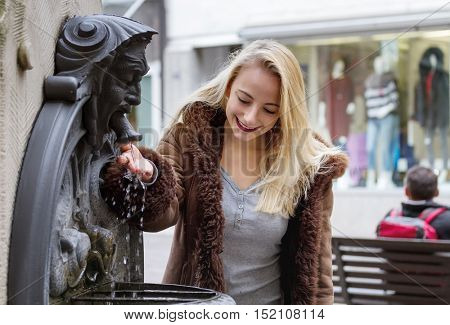 Young woman drinks water from a fountain