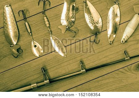 Fishing accessories for summer consisting of tackle bait lure jig hook. Wooden background. Outdoor activity and leisure concept. Toned.