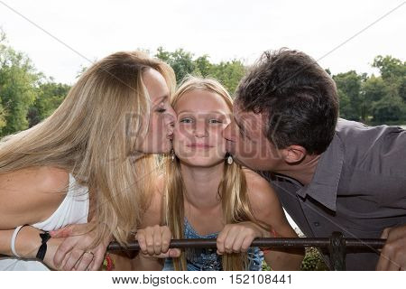 Smiling And Happy Family In A Garden Kissing