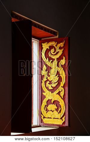 Buddhist church windows with wood carving of Thai traditional art.