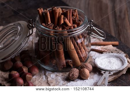 Cinnamon sticks in transparent glass jar. Nuts and sugar on rustic wooden background.
