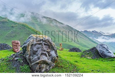 The monumental stone heads of the famous poets and writers in misty gorge of Sno Georgia.