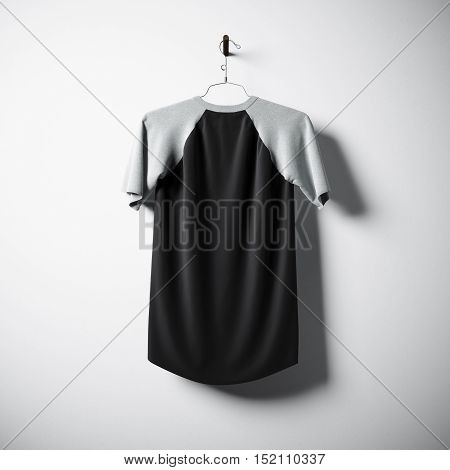 Blank cotton tshirt of black color hanging in center empty concrete wall. Clear label mockup with highly detailed textured materials. Square. Back side view. 3D rendering