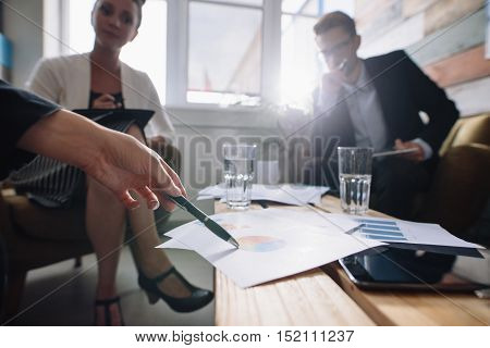 Shot of business people in a meeting at office with woman pointing at charts. Corporate professional discussing financial growth of the company.