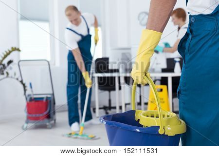 Image of person holding mop pail and man cleaning floor