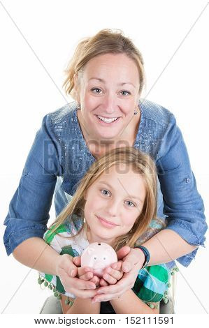 Happy Mother And Young Girl Holding Piggy Bank