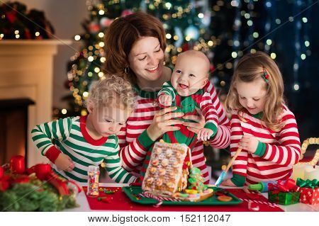 Happy family young mother with baby little boy and girl making gingerbread house at fireplace in decorated living room with Christmas tree. Baking and cooking with children for Xmas at home.