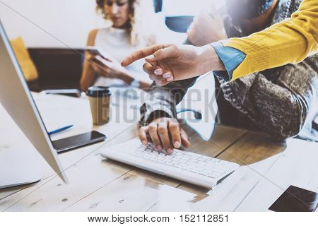 Group of coworkers working together in a sunny office.Man typing on computer keyboard at wood table.Female hand pointing to desktop screen.Horizontal image, blurred