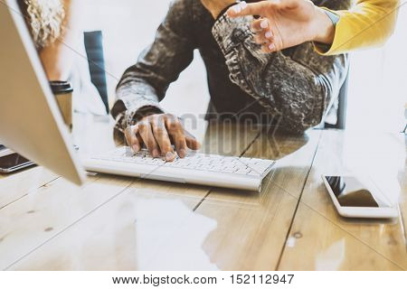 Coworking process in a sunny office.Man working on computer at the wood table.Female hand showing to desktop screen.Horizontal image, blurred