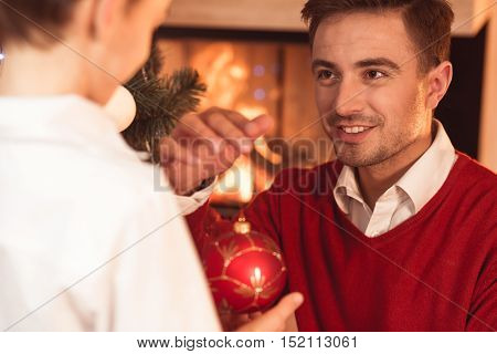 Close-up of man holding red Christmas bauble