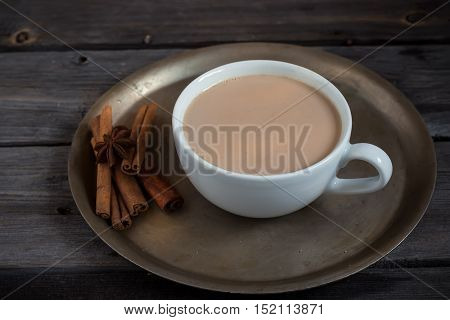Hot beverage in cup and spices. Style rustic. Copy space. Selective focus.