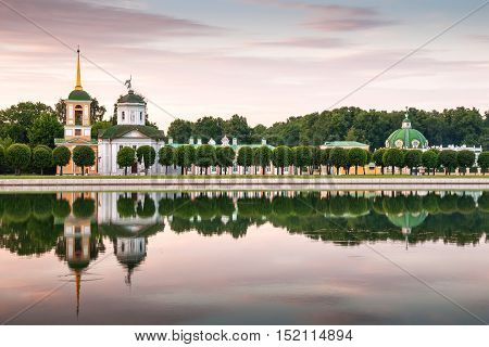 Church bell tower and reflection in pond at sunset in Kuskovo estate Moscow Russia.