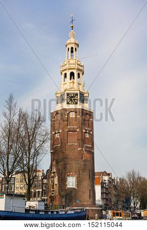 Grand old clock tower in Amsterdam, Netherlands against blue cloudy sky