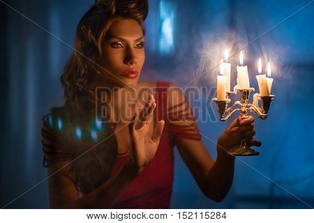 Woman looking on some red candles at night