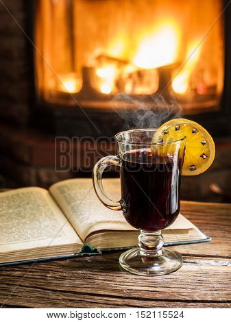 Hot mulled wine and a book on the wooden table. Fireplace with warm fire on the background.