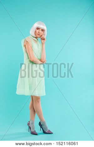 Full length of fashionable young woman in blonde wig standing and posing