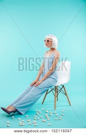Full length of beautiful young woman in sunglasses sitting on chair