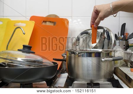 Female hand putting a carrot into a casserole on the stove messy kitchen in the blurred background