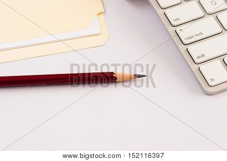 Business concept pencil with keyboard and file folder on white background