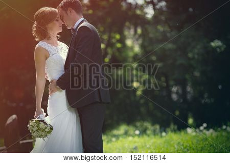 Beautiful young bride and groom kissing outdoors