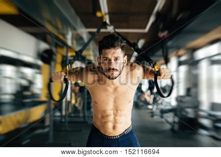 Determined handsome bodybuilder working out in gym