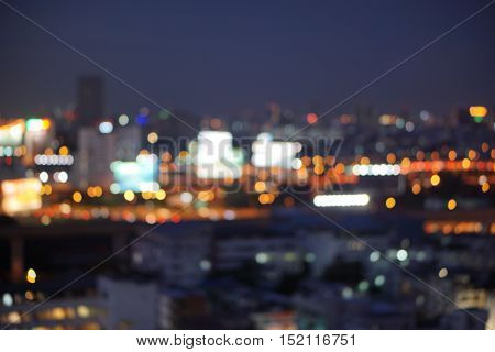 bird eye view  blur photo with bokeh light of high building, high way road, bill board and car in the dark night time